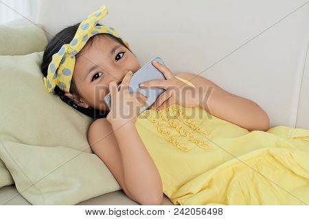 Lovely Pretty Shy Vietnamese Girl With Smartphone Lying On Sofa