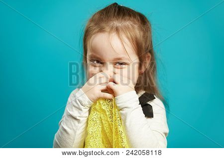 Laughing little girl covers her face with hands, smiles coquettishly and shyly, expresses embarrassment and shyness, portrait of cheerful female child on blue isolated background. poster