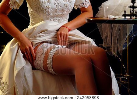 Wedding night preparing garter. Bride undressing and put veil on table. Candle illuminates house. Girl choosing stocking before wedding. Atelier for making wedding dresses. Role-playing game in bride.
