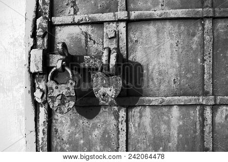 Part Of A Chained Gate With A Gate Valve And Two Locks Of An Old Historic Building. Black And White