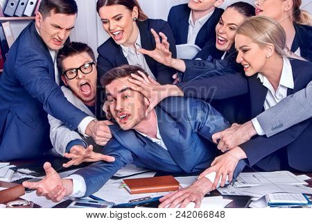 Business people office. Team people are unhappy with their leader. Intern man manager littered with work and does not cope with his duties. Businessman in stress. Approach to specific situation.