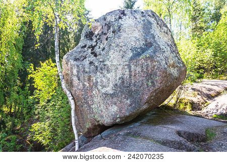 Huge stone hung on the edge of a cliff face in a wild park forest reserve poster