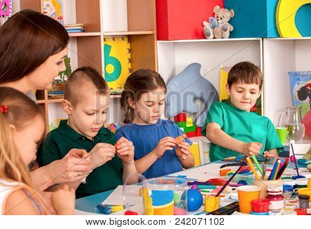 Child dough play in school. Plasticine for children. mold from plasticine in kindergarten .Kids knead modeling clay with hands in preschool. Teacher help roll some balls then press. Recovery.