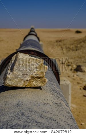 Focus on piece of silica rock on iron pipe stretching to horizon in Namib Desert carrying water supply from desalination plant in Swakopmund to uranium mine. Part of Chinese belt and road initiative. poster