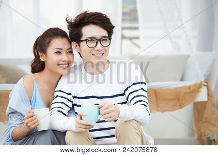 Cheerful Young Vietnamese Couple Enjoying Morning Coffee Together