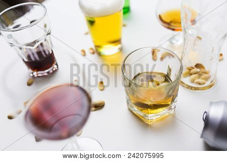 alcohol addiction and drunkenness concept - glasses of different drinks on messy table