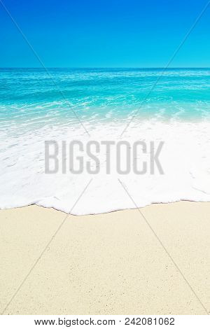 Beautiful Tropical  Beach With Soft Wave Of Blue Ocean, White Sand And Transparent Sky. Summer Trave
