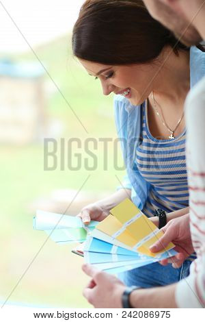 Couple Choosing Paint Colour From Swatch For New Home