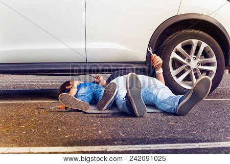 Father And Son Working Under Broken Car Together With Their Legs Sticking Out Outside