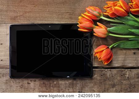 Overhead Shot A Blank Tablet With A Bouquet Of Orange And Yellow Tulips Over A Wood Table. Flat Lay