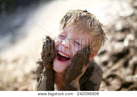 A Cute Little Boy Child Is Laughing As He Plays Outside In The Mud And Rubs Dirt On His Face With Hi