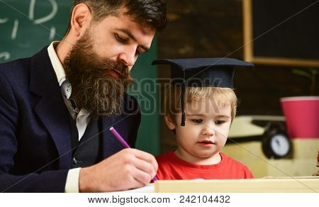 Homeschooling Concept. Enthusiastic Kid Studying With Teacher. Father Checking Homework, Helps To Bo