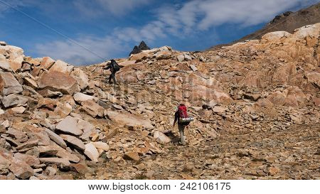 Two Men With Big Backpacks On, Hiking On Rocky Mountains, With Effort, On A Sunny Day, In The Wilder