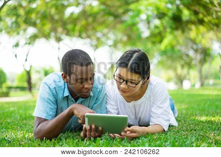 Serious Young Multiethnic Student Friends Using Touchpad. African American Man And Asian Woman In Gl