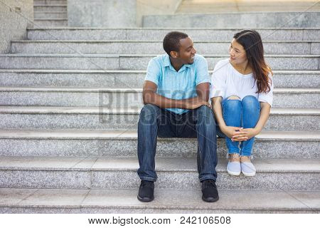 Smiling Mixed Race Man And Woman Sitting At Talking On Staircase. Young African American Man And Asi