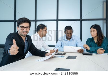 Happy Manager Showing Thumb-up While Colleagues Viewing Papers. Cheerful Sophisticated Male Business