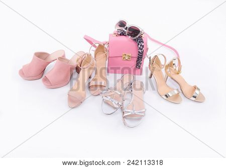Pile of various female shoes with handbag,scarf on white background
