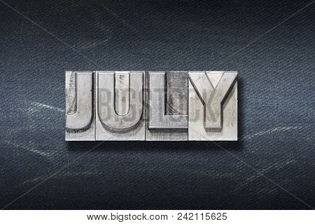 July Word Made From Metallic Letterpress On Dark Jeans Background