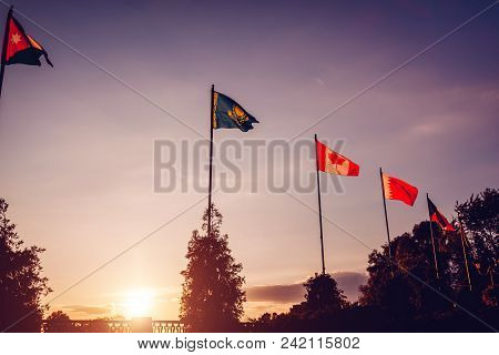 A Row Of Flying Flags Of Nations On Sunset Sky Background. Unity Of Nations. Flags Of Different Coun