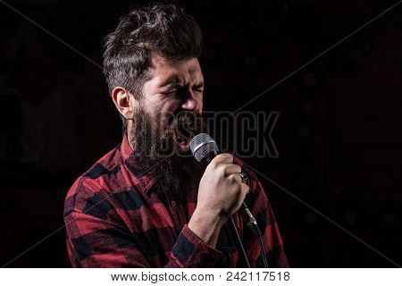 Talent Show Concept. Man With Tense Face Holds Microphone, Singing Song, Black Background. Musician