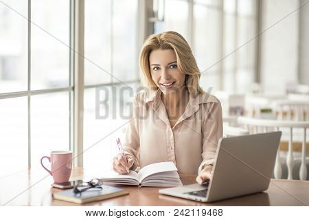 Young Blonde Woman In Cafe Sitting At Table Browsing Internet On Laptop Taking Notes On Project In P