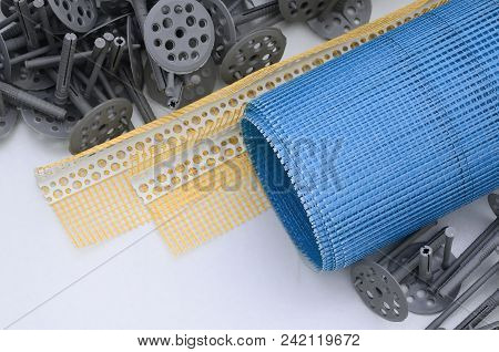 A Set Of Construction Items For The Insulation Of Walls. Plastic Dowels, A Roll Of Mesh For The Insu