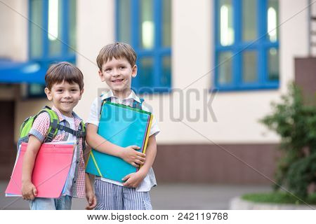 Cute Little School Students Briskly Talk On The Schoolyard. Children Have A Good Mood. Warm Spring M