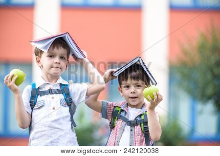 Child Going To School. Boy And His Friend Holding Books On Head Like House Roof On The First School