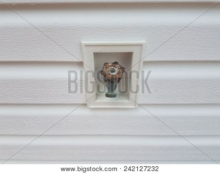 An Outdoor Water Spigot And White House Siding