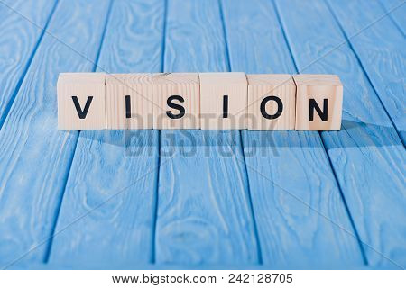 Close Up View Of Vision Word Made Of Wooden Blocks On Blue Tabletop