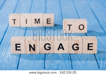 Close Up View Of Arranged Wooden Blocks Into Time To Engage Phrase On Blue Wooden Surface
