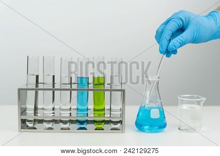 Laboratory Scene, The Scientist Holding The Glass Stirring Rod. Flask, Test Tubes In The Rack And Be