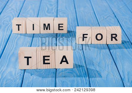 Close Up View Of Arranged Wooden Blocks Into Time For Tea Phrase On Blue Wooden Surface