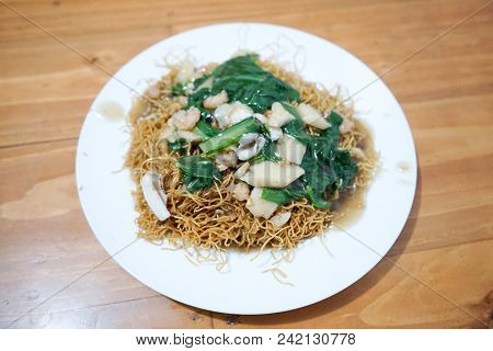 Seafood Vermicelli Noodle With Shrimp, Squid, And Vegetable Stir On Dish Wood Table