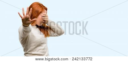 Beautiful young redhead woman stressful and shy keeping hand on head, tired and frustrated isolated over blue background