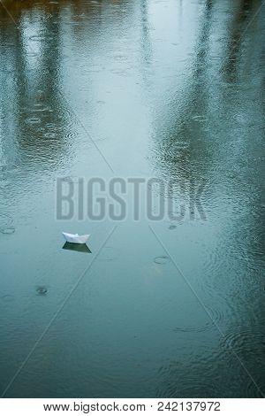 origami boat on wet asphalt during rain in summer poster