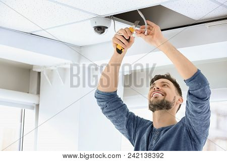 Technician Installing Cctv Camera On Ceiling Indoors