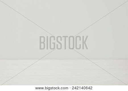 View Of Empty Wooden Surface With White Wall
