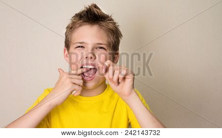 Boy Flossing Teeth. Close-up Portrait Of Teen Boy With Dental Floss Isolated.