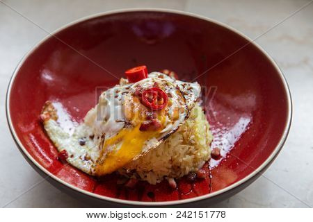 Asian fried rice topped with a sunny side egg and chilli