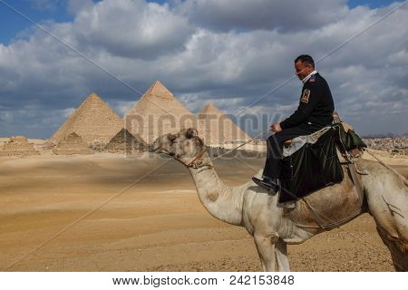 Cairo / Egypt - January 02 2016: A Police officer rides his camel in Giza Pyramids area. Camel riding policemen are a traditional part of the Pyramids area.