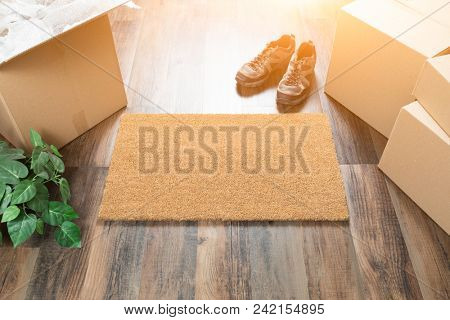 Blank Welcome Mat, Moving Boxes, Shoes and Plant on Hard Wood Floors.
