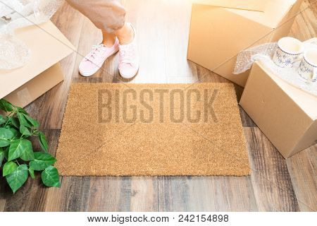 Woman in Pink Shoes and Sweats Standing Near Home Sweet Home Welcome Mat, Boxes and Plant.