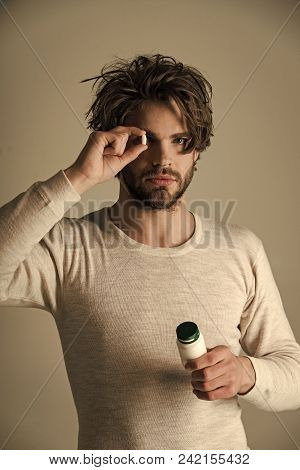 Man looking at camera. Handsome man face. Health and medicine, hangover. Cold, flu and headache treatment, hypnotic tablet. Man with pills in jar. Drug and antidepressant, insomnia. Dieting pill and vitamin, man with anabolic. poster