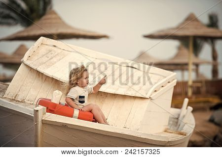 Happy Kid Having Fun. Child Little Boy Little Sitting In Life Buoy On Boat. Small Kid Pointing With