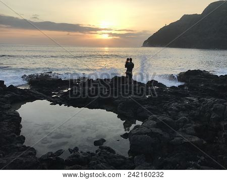 Father And Child Watching The Sunrise In Oahu, Hawaiian Islands.