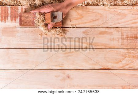 Hand Catch Is Carpenter Plane On A Wooden Board Using Smoothing.