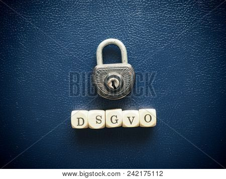 Old Used Padlock With Wooden Dices, Gdpr Or Dsgvo Concept On A Blue Background
