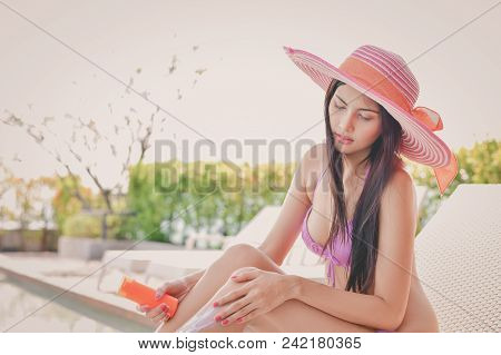 Swimsuit Concept. Beautiful Girl In Swimsuit Is Applying Sunscreen. Beautiful Girl In A Swimsuit Pro