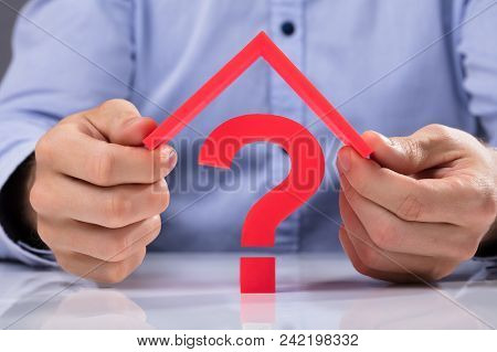 Businessperson Holding Roof Over Question Mark Sign
